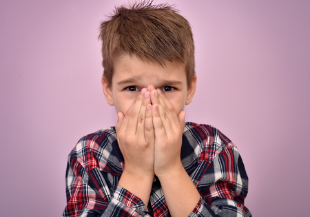 Scared young boy with hands on his face