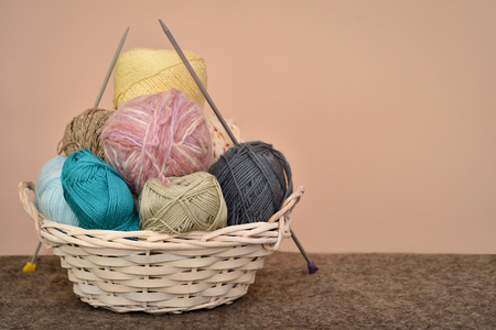 Knitting accessories in the basket on the woolen background
