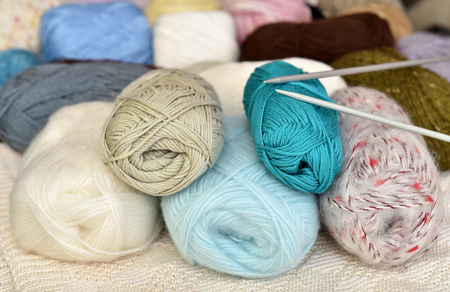 Multicolored knitting spools of wool and thread and knitting needles Banco de Imagens