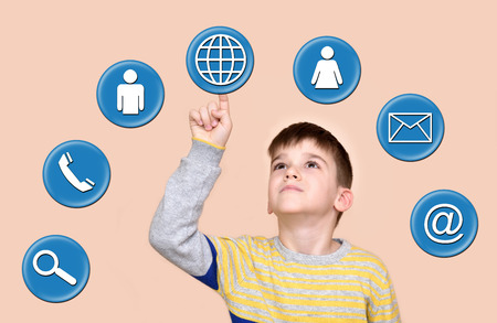 Young boy touching globe button on a virtual touch screen Stock Photo