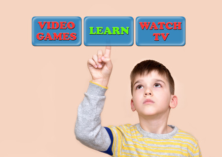 Young boy touching learn button on a virtual touch screen