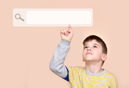 Young boy touching search button on a virtual touch screen