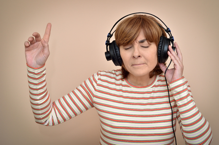 Happy middle aged woman with headphones and closed eyes listening to music and enjoying