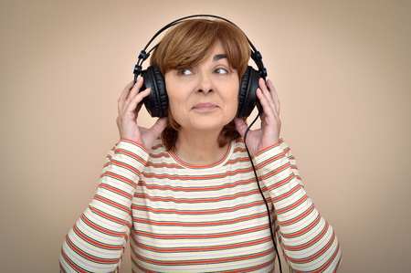 Happy middle aged woman with headphones listening to music and enjoying