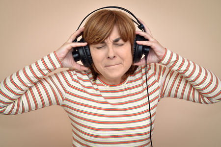 Displeased middle aged woman with headphones and closed eyes listening to very loud music