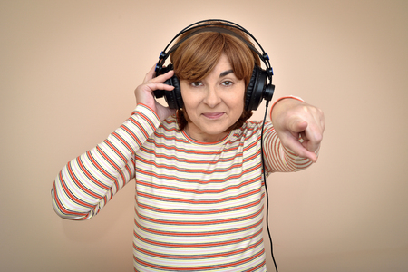 Smiling middle aged woman with headphones pointing her index finger at the camera