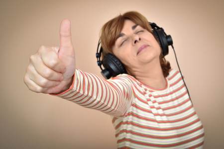 Smiling middle aged woman with headphones showing thumb up. Selective focus.