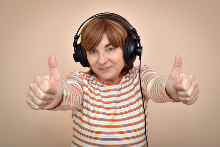 Smiling middle aged woman with headphones showing thumbs up Banco de Imagens