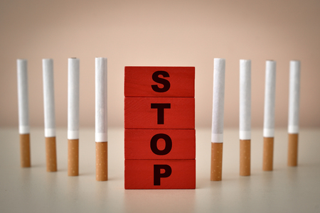Red wooden blocks with word stop and cigarettes. Stop smoking concept. Selective focus.