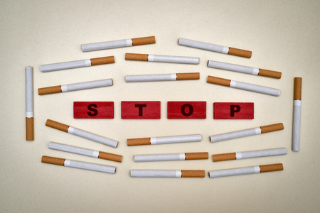 Red wooden blocks with word stop and cigarettes. Stop smoking concept. Top view.