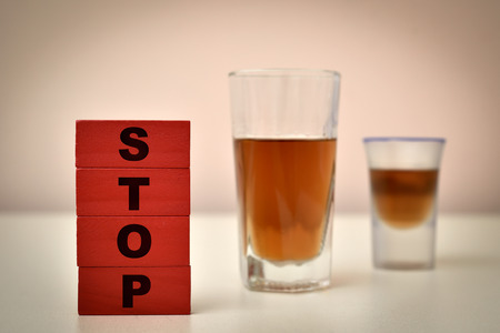 Red wooden blocks with word stop and glasses of alcohol. Stop alcohol concept. Selective focus. Banco de Imagens
