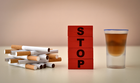 Red wooden blocks with word stop, heap of cigarettes and glass of alcohol. Stop addiction concept. Selective focus.