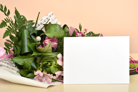 Bouquet of flowers and blank greeting card. Selective focus.