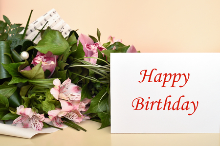 Bouquet of flowers and greeting card with Happy Birthday message. Selective focus.