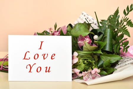 Bouquet of flowers and greeting card with I Love You message. Selective focus. Banco de Imagens