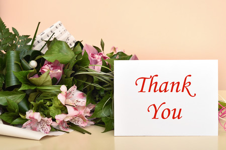 Bouquet of flowers and greeting card with Thank You message. Selective focus. Banco de Imagens