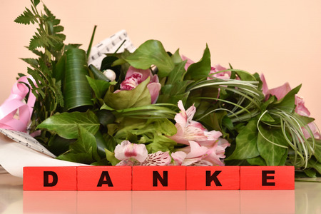 Bouquet of flowers and red wooden blocks with Danke message. Selective focus.
