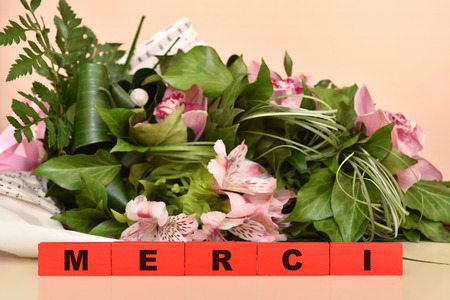 Bouquet of flowers and red wooden blocks with Merci message. Selective focus. Banco de Imagens