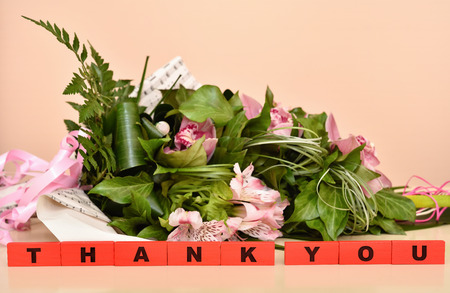 Bouquet of flowers and red wooden blocks with Thank You message. Selective focus.
