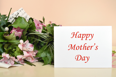 Bouquet of flowers and greeting card with Happy Mother's Day message. Selective focus.
