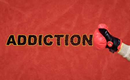 Human fist with a boxing glove hitting and breaking word addiction on the dirt and scratches red background