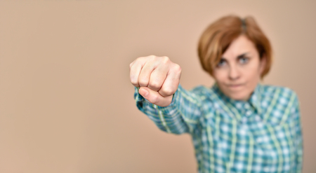 Fist of an angry woman throwing a punch isolated on the background. Copy space on the left side. Selective focus.