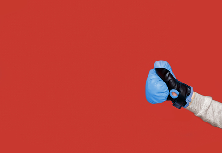Human fist with a blue boxing glove isolated on the red background. Copy space on the left side.