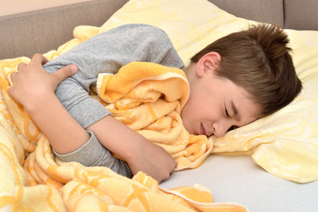 Ill cute young boy with closed eyes lying in bed