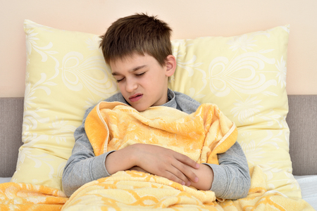 Ill cute young boy with closed eyes sitting in bed leaning on the pillow Banco de Imagens