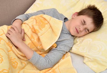 Ill cute young boy with closed eyes lying in bed holding his stomach