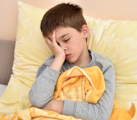 Ill cute young boy with closed eyes sitting in bed holding his head