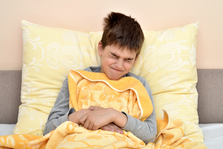 Ill cute young boy with closed eyes sitting in bed holding his stomach