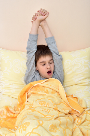 Cute young boy sitting in bed leaning on the pillow, yawning and stretching after waking up
