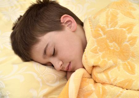 Cute young boy sleeping in bed. Close-up. Banco de Imagens