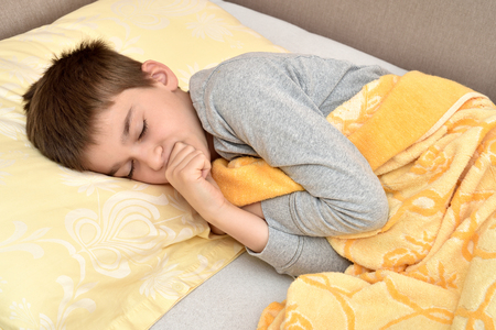 Cute young boy sleeping in bed Banco de Imagens