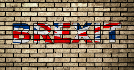Graffiti BREXIT in the colors of the UK flag on the brick wall. Brexit concept. Banco de Imagens