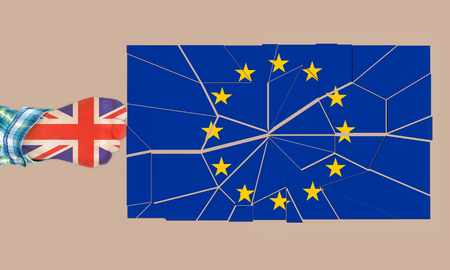 Fist of a woman in the colors of the UK flag hitting and breaking the European union flag. Brexit concept.