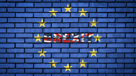 Word BREXIT in the colors of the UK flag inside European union yellow stars on the blue brick wall texture. Brexit concept. Banco de Imagens