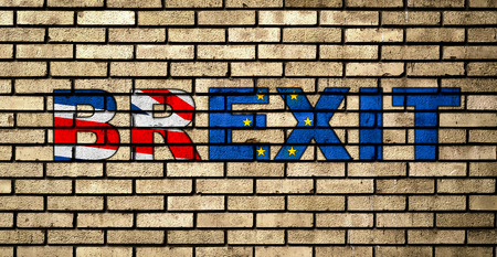 Graffiti BREXIT in the colors of the UK and European union flags on the brick wall. Brexit concept. Banco de Imagens