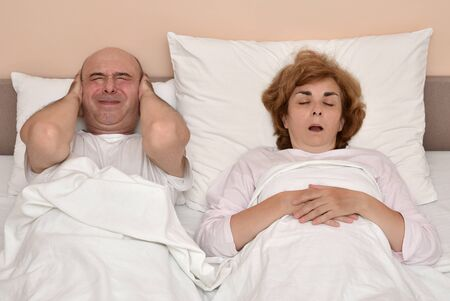 Couple in bed. Woman snoring while man is covering his ears with hands. Stockfoto