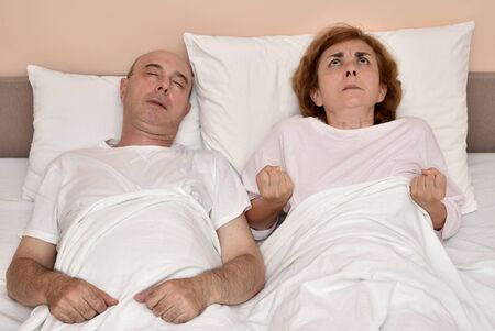 Mature couple in bed. Husband sleeping while his angry wife is looking up and clenching fists. Family crisis concept. Banco de Imagens - 129949916