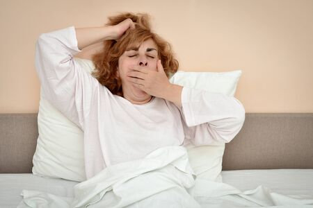 Exhausted and tired mature woman in bed waking up, stretching and yawning Stockfoto