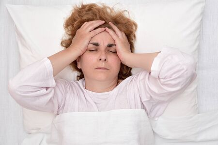 Exhausted and tired mature woman with severe headache lying in bed and holding her head. Top view.