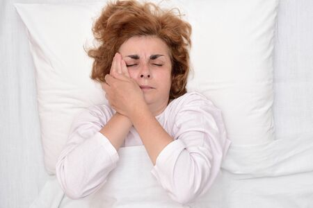 Mature woman with toothache lying in bed and holding her cheek. Top view. 写真素材