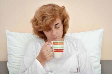 Exhausted and tired mature woman sitting in bed and barely holding a mug