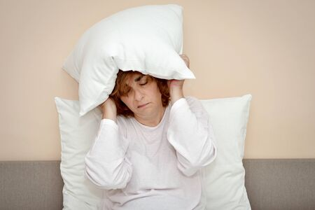 Exhausted and tired mature woman with closed eyes sitting in bed with pillow over her head