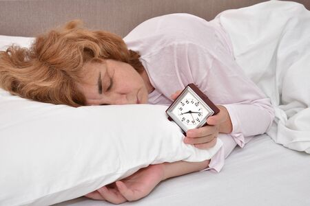 Exhausted and tired mature woman sleeping in bed and holding a clock. She cannot wake up. Banque d'images - 129949933