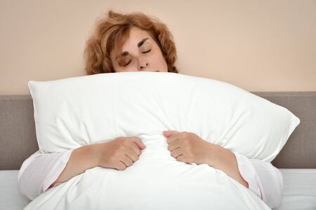 Tired and exhausted mature woman with closed eyes sitting in bed and hugging a pillow with her hands
