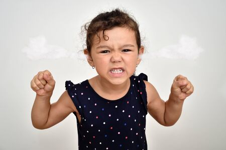 Angry and aggressive young girl with clenched teeth and fists and steam blowing out of her ears looking at the camera