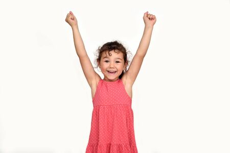 Happy and smiling cute young girl with hands up looking at the camera